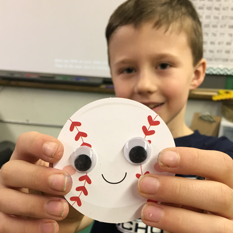 a paper baseball with googly eyes