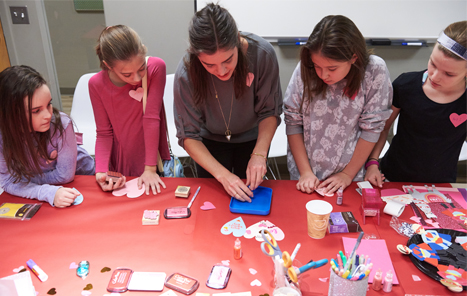 many young girls around a table crafting