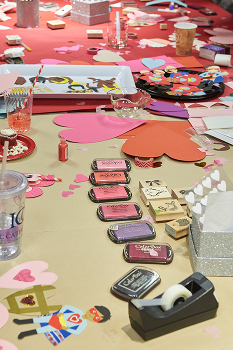a large table covered in crafting supplies and materials to make valentines