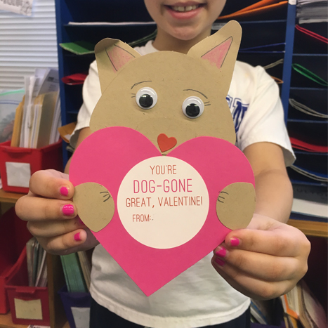 a paper valentine of a cat holding a heart