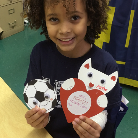 a child holding up two hand made valentines