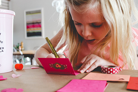 a child writing in a valentine's day card
