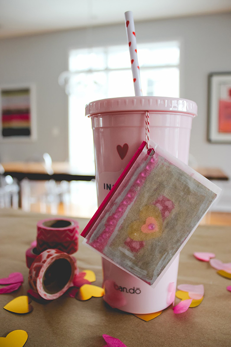 a pink cup with a valentine attached