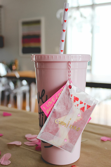 a pink cup with a goody bag attached