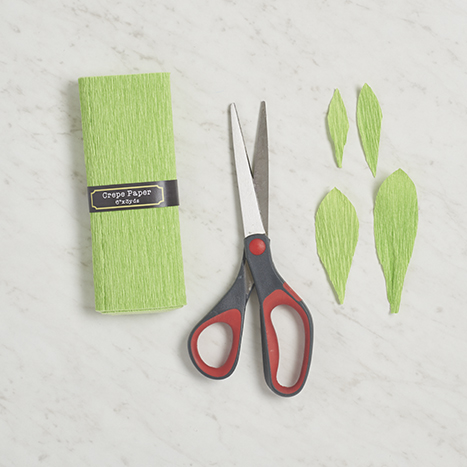green crepe paper, scissors, and paper leaves