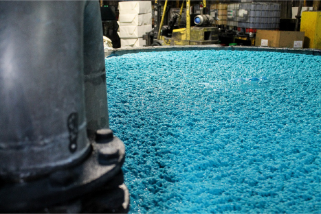 a vat of lagoon colored paper pulp