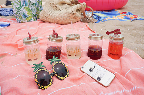 drinks in mason jars on a beach towel