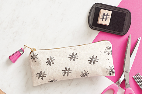 canvas pouch with hashtags stamped on it and a pink tassel