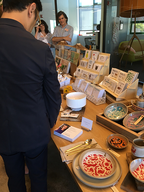man looking at a table with ceramics on it